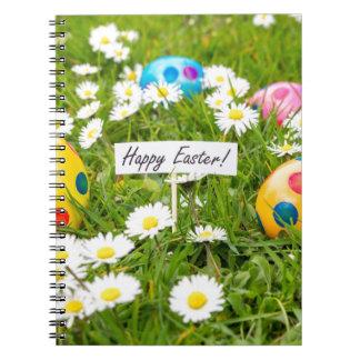 Cadernos Ovos da páscoa pintados na grama com margaridas