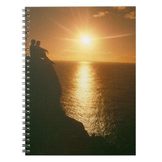 Cadernos por do sol romântico pela praia