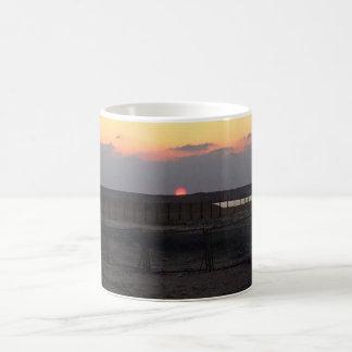 café & canecas de viagem do por do sol