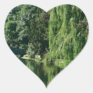 Caminhada ensolarada verde do rio das árvores do adesivo coração