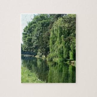 Caminhada ensolarada verde do rio das árvores do quebra-cabeça