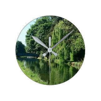 Caminhada ensolarada verde do rio das árvores do relógio redondo
