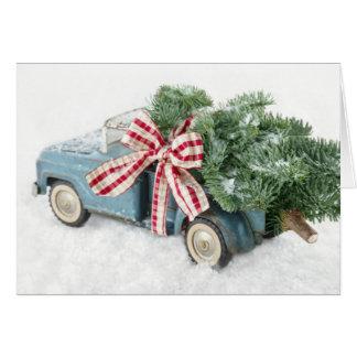 Caminhão azul do brinquedo que leva uma árvore de cartão comemorativo