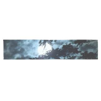 Caminho De Mesa Pequeno A lua ilumina a noite atrás dos ramos de árvore
