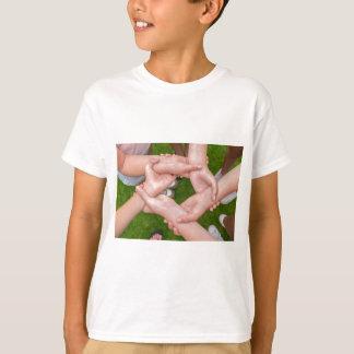 Camiseta Braços com mãos das meninas que guardaram-se
