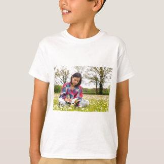 Camiseta Escrita da mulher no prado com flores do primavera
