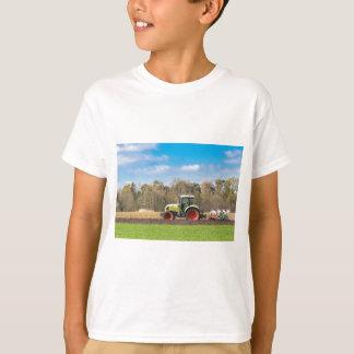 Camiseta Fazendeiro no trator que ara o solo arenoso no