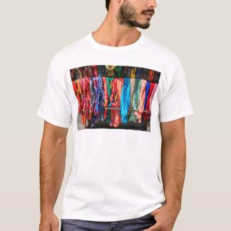 Camiseta Muitos scarves coloridos que penduram no mercado