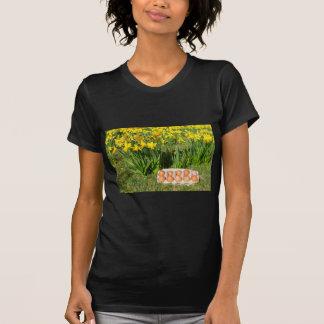 Camiseta Ovos na caixa na grama com daffodils amarelos