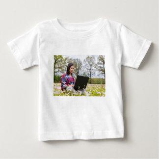 Camiseta Para Bebê A mulher senta-se com o laptop no prado de