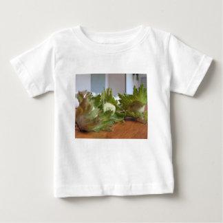 Camiseta Para Bebê Avelã verdes frescas em uma mesa de madeira