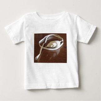 Camiseta Para Bebê Carregador branco do smartphone na mesa de madeira