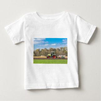 Camiseta Para Bebê Fazendeiro no trator que ara o solo arenoso no