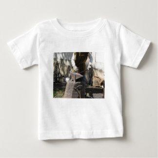 Camiseta Para Bebê Ferreiro que forja manualmente o metal derretido