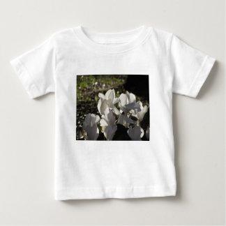 Camiseta Para Bebê Flores brancas do cyclamen de Backlits no fundo