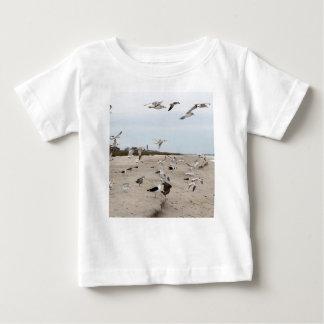 Camiseta Para Bebê Gaivotas que voam, estando e comendo na praia
