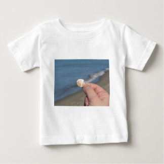 Camiseta Para Bebê Guardarando um seashell na mão
