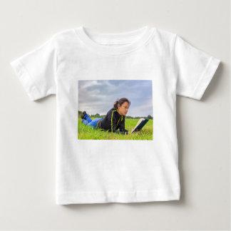 Camiseta Para Bebê Jovem mulher que encontra-se no livro de leitura