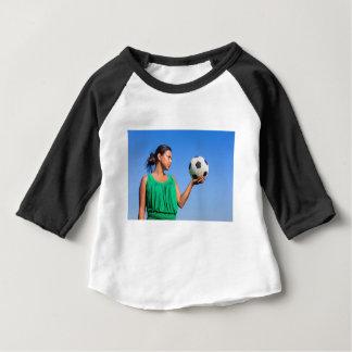 Camiseta Para Bebê Jovem mulher que guardara o futebol na mão com céu