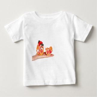 Camiseta Para Bebê Mão com modelo humano do coração em background.jp