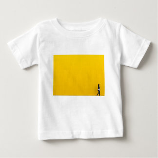 Camiseta Para Bebê Menina que anda contra a parede amarela enorme