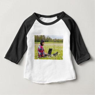 Camiseta Para Bebê Mulher que senta-se com o laptop no prado do