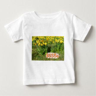 Camiseta Para Bebê Ovos na caixa na grama com daffodils amarelos
