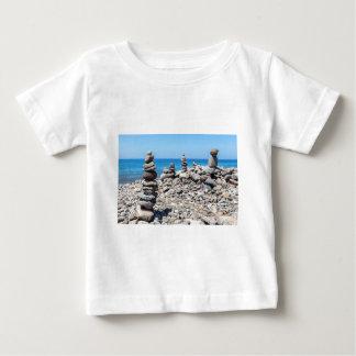 Camiseta Para Bebê Pedras empilhadas da praia no mar azul