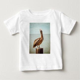 Camiseta Para Bebê Pelicano bonito empoleirado sobre o oceano
