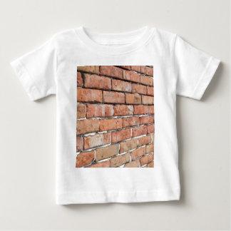 Camiseta Para Bebê Vista de uma parede de tijolo velha com um borrão
