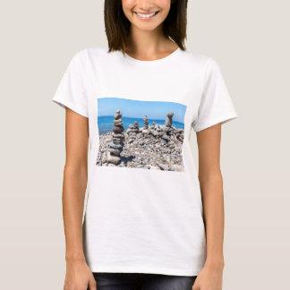 Camiseta Pedras empilhadas da praia no mar azul