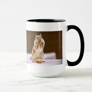 Caneca Chipmunk bonito que come um amendoim