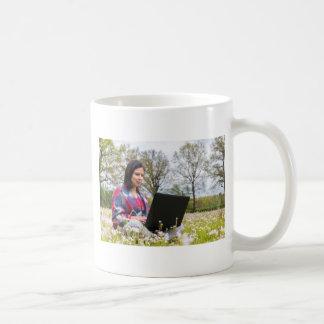Caneca De Café A mulher senta-se com o laptop no prado de