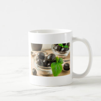 Caneca De Café Brown conservou azeitonas no fundo de madeira
