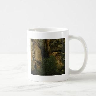 Caneca De Café cara amarela da rocha com árvores