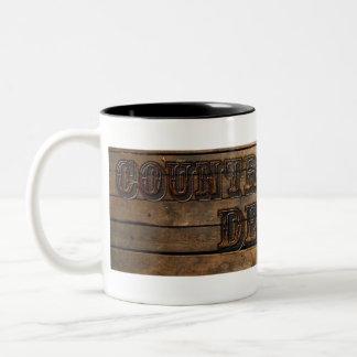 Caneca De Café Em Dois Tons O país dois ocidentais tonificou o copo de café