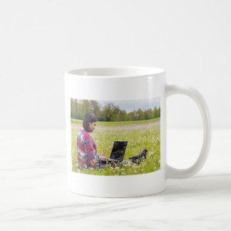 Caneca De Café Mulher que senta-se com o laptop no prado do
