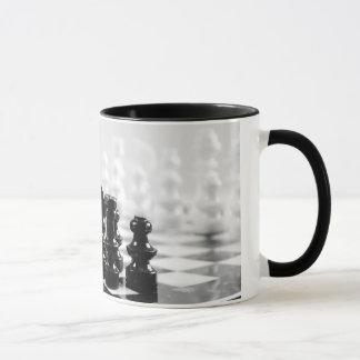 Caneca de café preto e branco do tabuleiro de