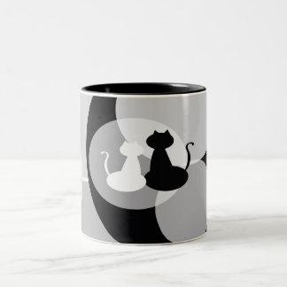 Caneca graciosa dos gatos brancos e pretos
