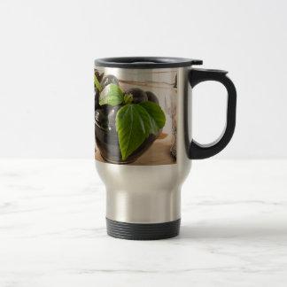 Caneca Térmica Azeitonas pretas em uma mesa e em copos do vidro