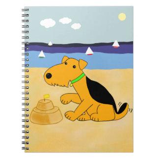 Cão bonito de Kawaii Airedale no caderno da praia
