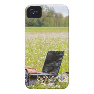 Capinha iPhone 4 Mulher que senta-se com o laptop no prado do