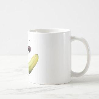Cara da fruta da banana em uma caneca de café