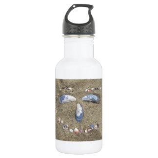 Cara da garrafa de água feita na areia com escudos