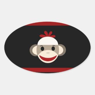 Cara de sorriso bonito do macaco da peúga no preto adesivos em formato ovais