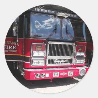 Carro de bombeiros vermelho na garagem adesivo redondo