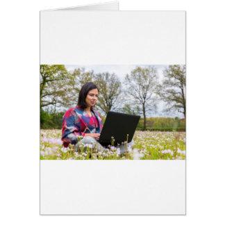 Cartão A mulher senta-se com o laptop no prado de