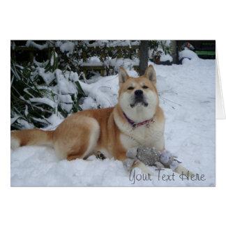 Cartão Akita vermelho bonito na neve com o brinquedo do