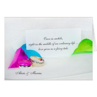 Cartão alianças de casamento com pétalas cor-de-rosa