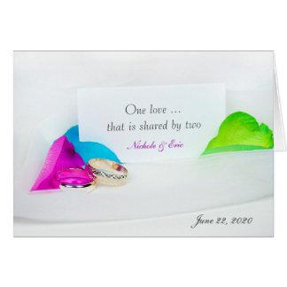 Cartão alianças de casamento e pétalas cor-de-rosa